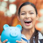 30721621 - closeup portrait happy, smiling business woman, bank employee holding piggy bank, isolated outdoors indian autumn background. financial savings, banking concept. positive emotions, face expressions